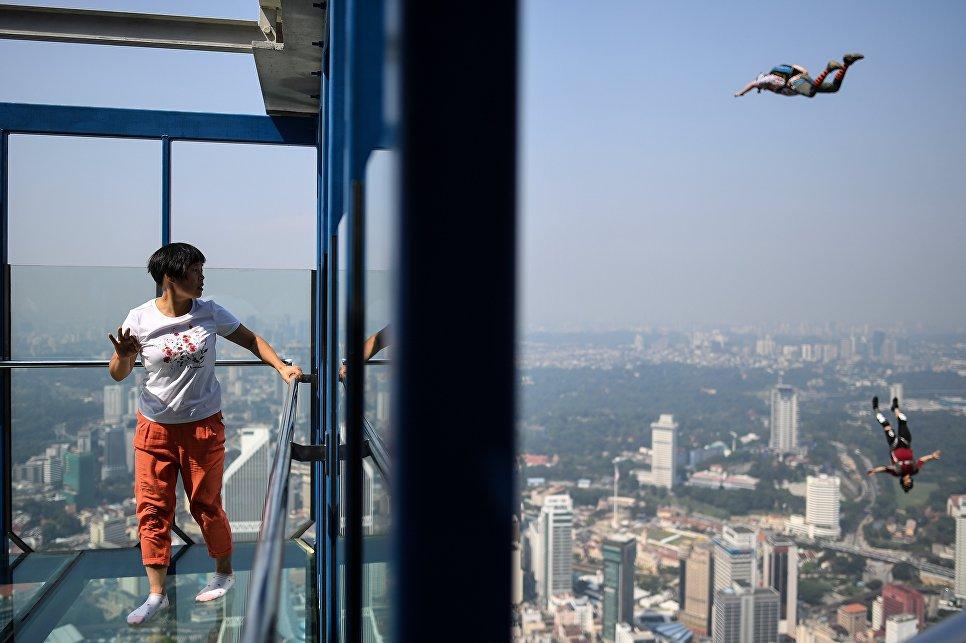 Туристка наблюдает за прыжком бейсджамперов с небоскреба в Куала-Лумпуре, Индонезия