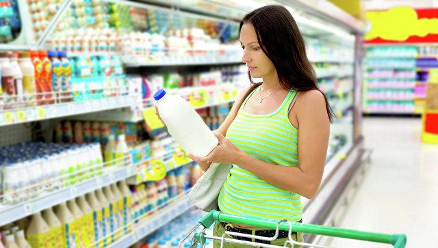 Женщина выбирает молочную продукцию в магазине