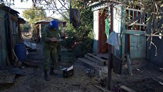 Сотрудник Совместного центра контроля и координации режима прекращения огня изучает последствия обстрела поселка Марьевка в Донецкой области. Архивное фото