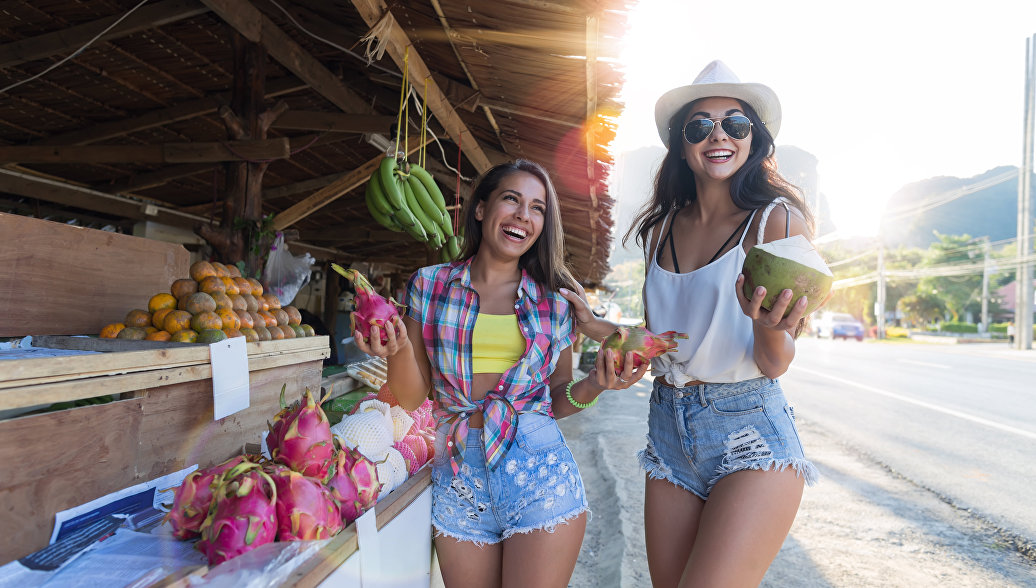 Девушки покупают экзотические фрукты в Таиланде