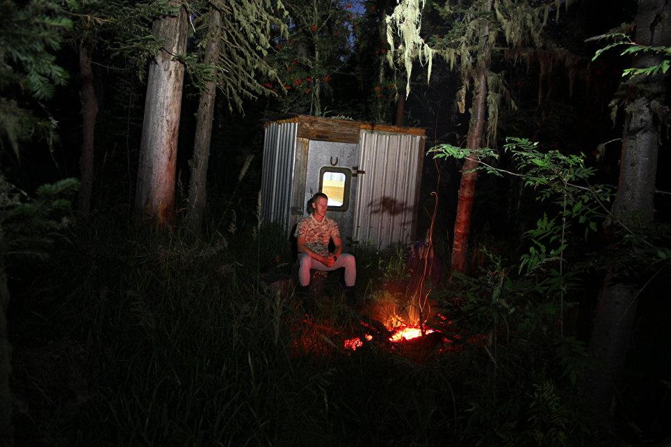 Андрей Абвгат в тайге ночью у железной избы.