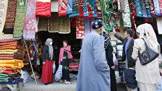 Уйгурские мусульмане выбирают молельные коврики на рынке в Хотане