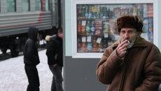 Мужчина курит на платформе железнодорожного вокзала Омска