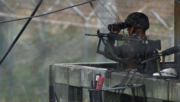 Южнокорейский солдат смотрит в сторону КНДР с наблюдательного пункта
