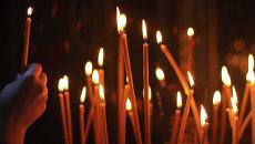 Мужчина ставит свечу в церкви. Архив