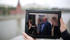 На экране планшета фотография момента, как экс-сотрудник ЦРУ Эдвард Сноуден в сопровождении адвоката Анатолия Кучерены покидает здание аэропорта Шереметьево, архивное фото