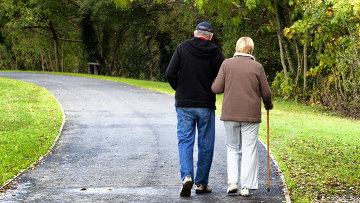 Пожилая пара гуляет в парке