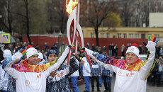 Олимпийский чемпион по фигурному катанию Алексей Урманов (слева) во время эстафеты Олимпийского огня в Петербурге.