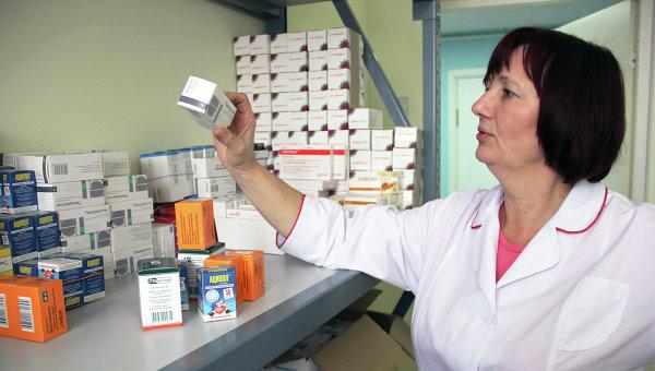 Сотрудница томского центра Анти-СПИД разбирает лекарства для ВИЧ-положительных людей. Архивное фото