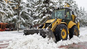 Экскаватор убирает снег, архивное фото