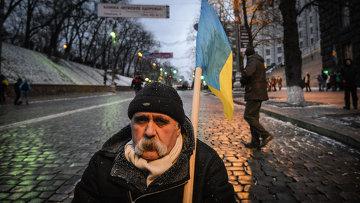 Мужчина с флагом Украины возле здания кабинета министров Украины в Киеве
