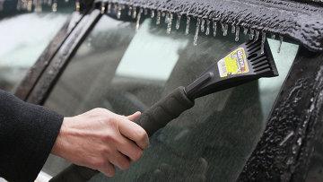 Мужчина счищает наледь со стекла автомобиля. Архивное фото