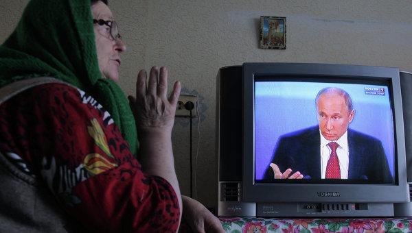 Жительница деревни Фрунзе Омской области смотрит телетрансляцию пресс-конференции президента России Владимира Путина.